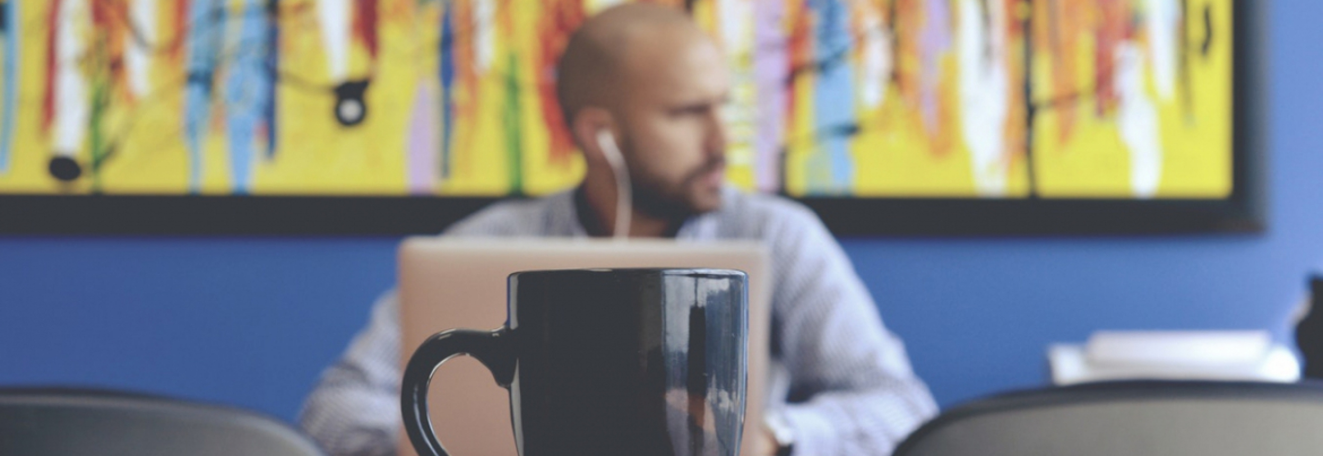 Man plugged into laptop sitting across from coffee mug